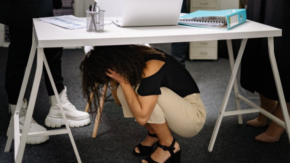 Jovem se esconde embaixo da escrivaninha com medo do futuro